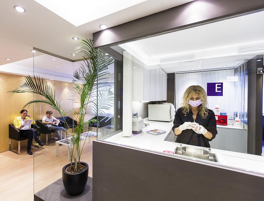 Sala de Espera y Sala de Esterilización de la Clínica Dental Ochogavía en Palma con dos pacientes esperando su turno y una enfermera trabajando