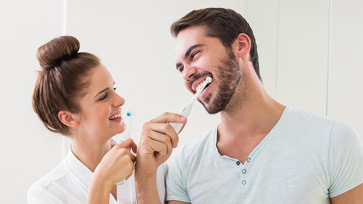 pareja cepillándose los dientes según consejos de la clínica dental ochogavía