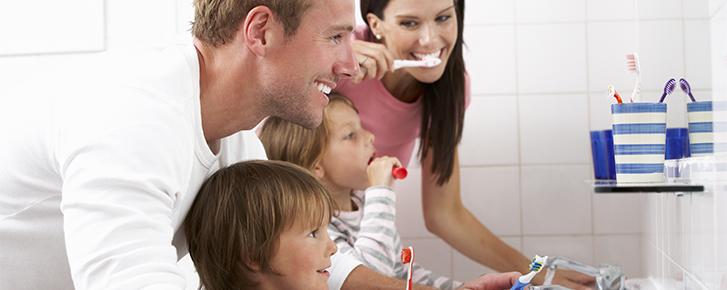 Familia cepillándose los dientes según los consejos de la clínica dental ochogavía de Palma de Mallorca