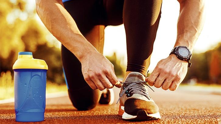 Corredor con buena salud dental atandose los cordones antes de comenzar a correr